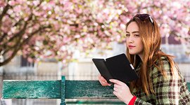 Young woman reading a tablet on a bench