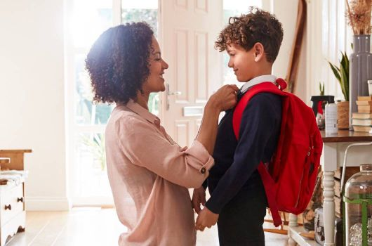 Woman adjusting school boys tie before he sets off for school