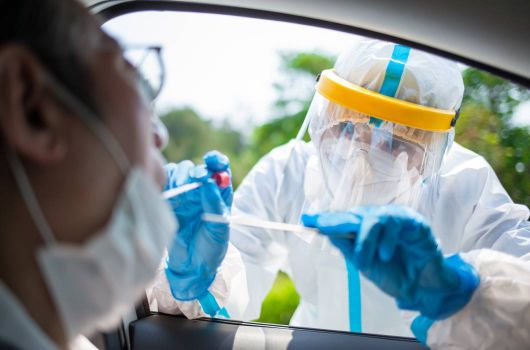 Person in PPE taking swab from someones mouth whilst sat in the car