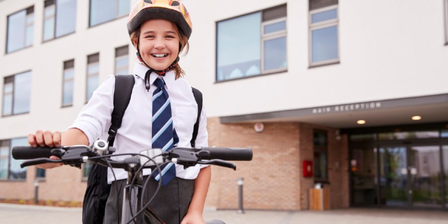 School girl standing with a bicycle