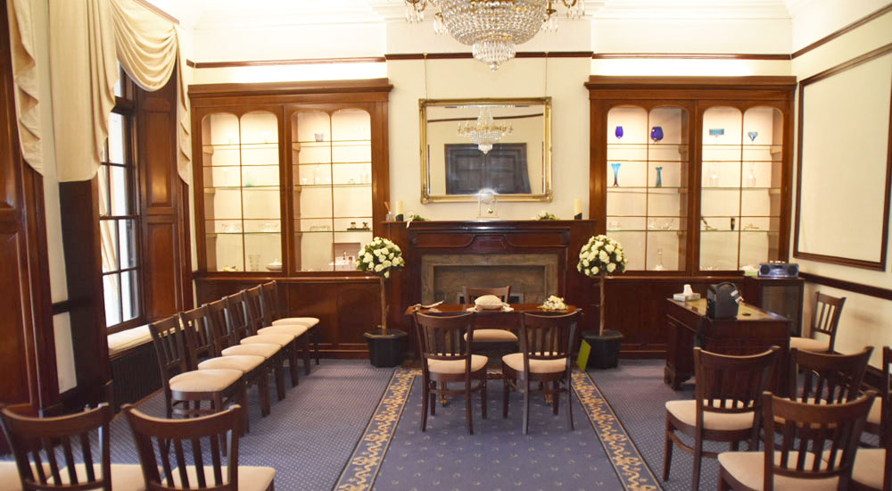 Ceremony room at Leatherhead Register Office featuring display cabinets and chandelier.