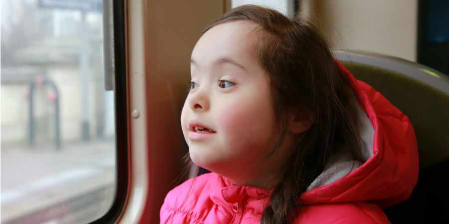 Downs syndrome girl on bus in pink coat