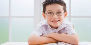 Young schoolboy smiles at camera, arms folded over a workbook