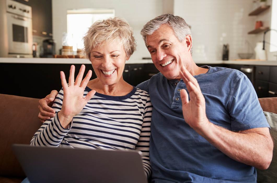 Two people sitting on a sofa and waving at a laptop screen
