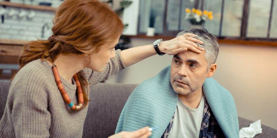 Woman feeling temperature of mans head with her hand