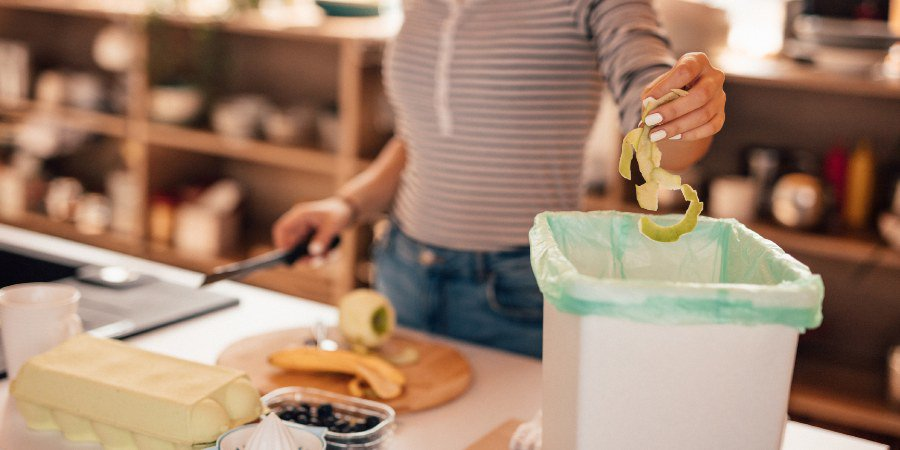 Image of woman putting food waste in a bin