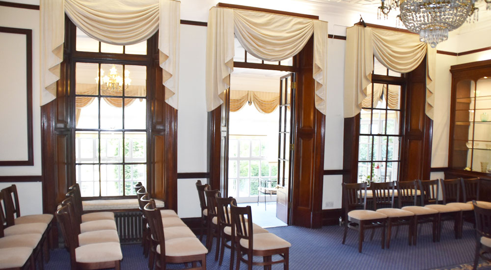 Ceremony room at Leatherhead Register Office featuring chandelier and large windows opening into the conservatory.