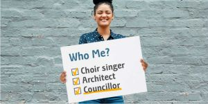 Young female holding up sign with tick boxes of choir singer, architect, councillor