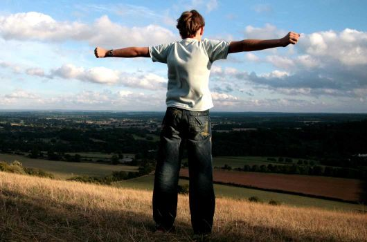 Boy standing on hill with arms outstretched