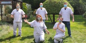 Homemade heros wearing scrubs and PPE in garden