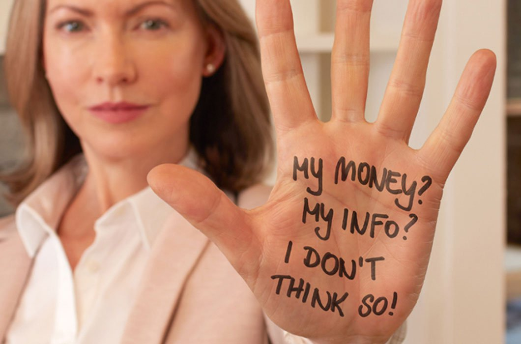 Image of lady holding up her hand on which are written prompts to deter being scammed