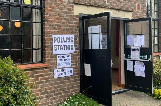 Doors open for polling station in village hall with disabled access sign and opening hours