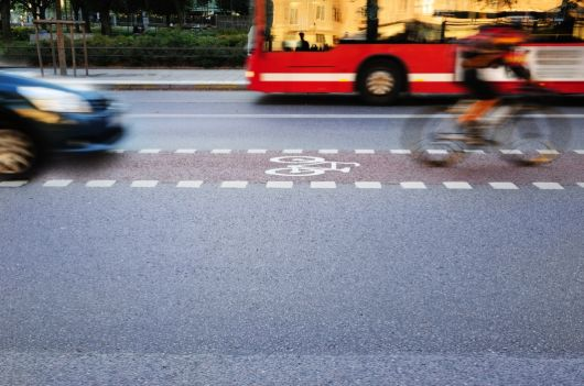 Image of bus, car and cyclist moving down a road in a blur of speed