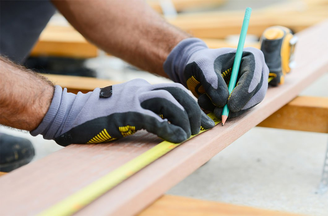 Image of workman, specifically capenter measuring wood plank