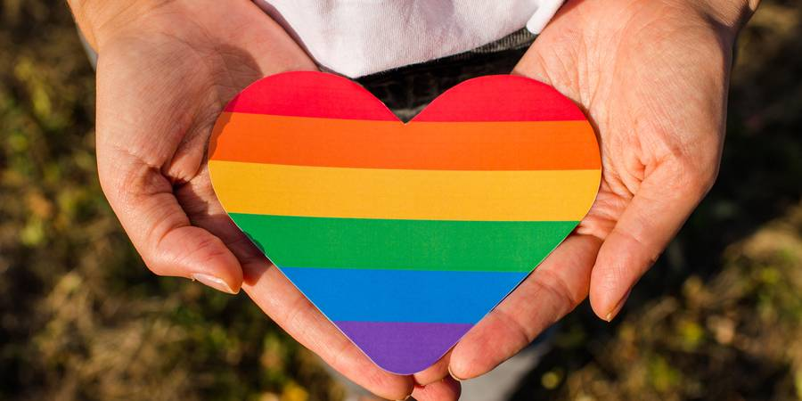 Image of hands holding a rainbow heart