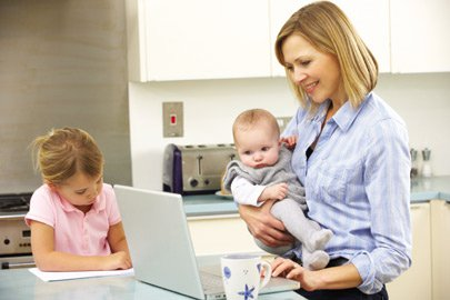 Mother holding a baby whilst using a laptop