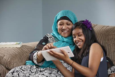 Woman and girl looking at a tablet and sharing a joke.
