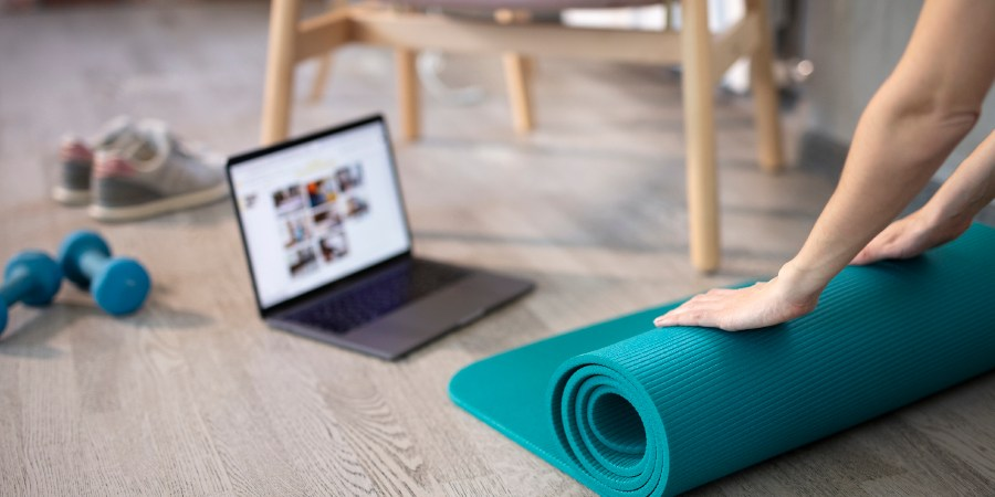 Image of yoga mat and laptop on the floor