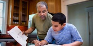 Social worker helps boy with work at the kitchen table