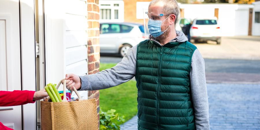 Image of man wearing a face covering handing shopping to a resident at their front door