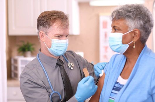 Doctor giving patient injection with masks on