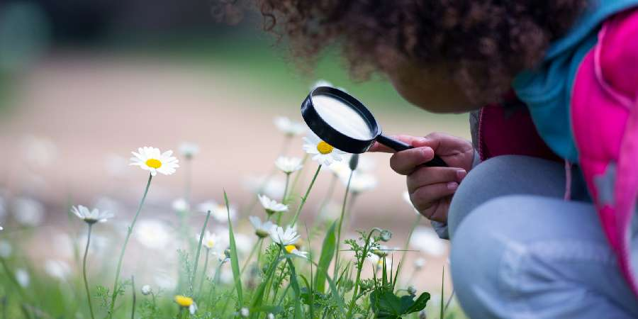 Image of girl looking through magnifying glass