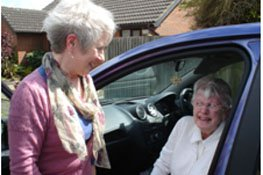Two older people chatting, one is sitting in a car