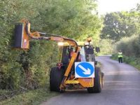 A tractor, with a hedge cutting attachment, cutting a roadside hedge