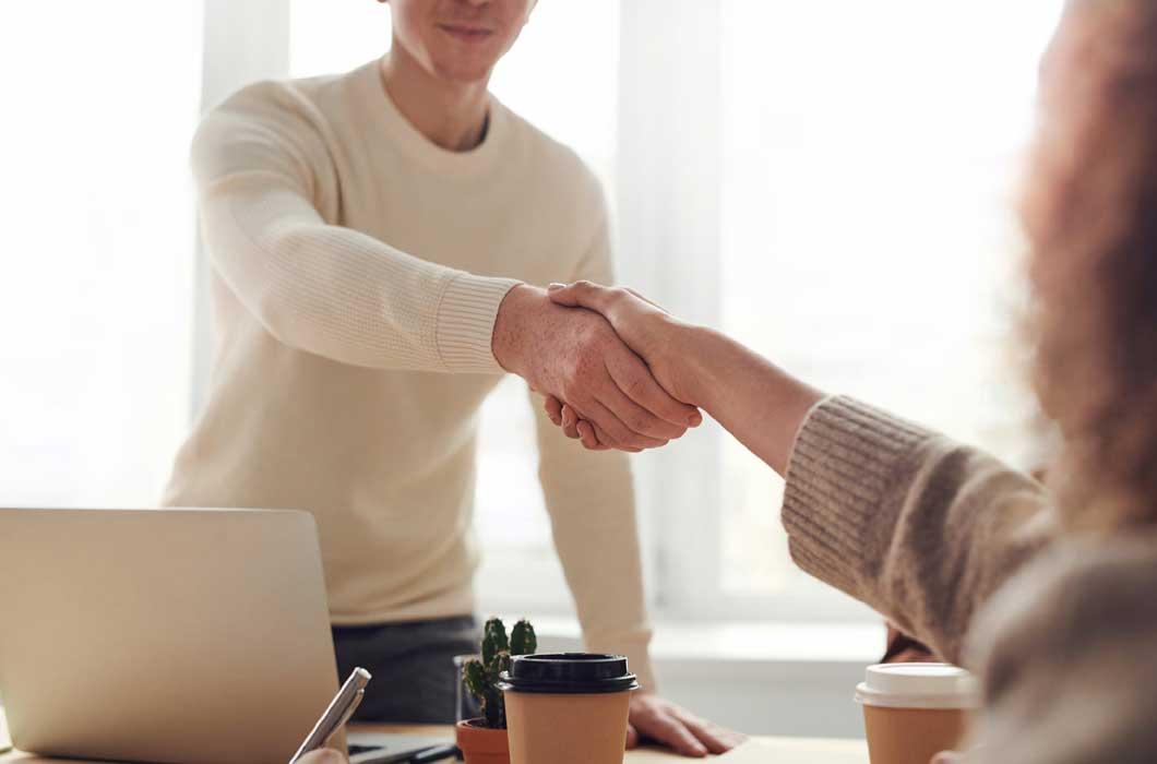 Two people shaking hands across an office desk