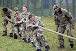 Young people in military outfits doing a tug of war