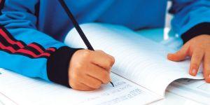 Boy writes in workbook