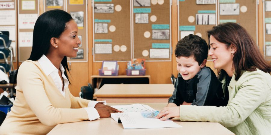 Mother and son discuss something with a teacher, over a table of paperwork