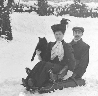 Young couple with dog enjoying the snow, c.1900. (Photographer not known). Surrey History Centre reference: 4527/1/19.