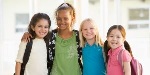 Four primary and infant school girls smile at camera