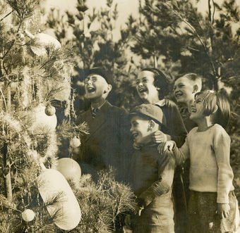 Carols round the Christmas Tree'. Photograph of children at Goldsworth Nurseries, Woking, c.1930. (Photograph by Fox Photos of London). Surrey History Centre reference: 7562/7/2 (1).