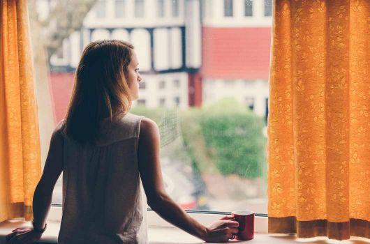Woman looking out of the window bored