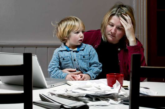 Woman looking stressed with young child on her lap