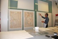 maps attached to a wall with a man working on them