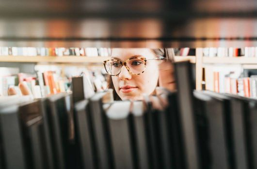 Woman looking through shelves of library books