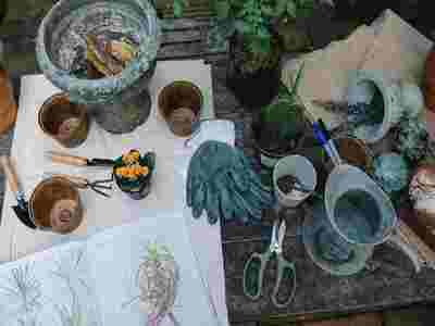 small gardening tools and gloves on table
